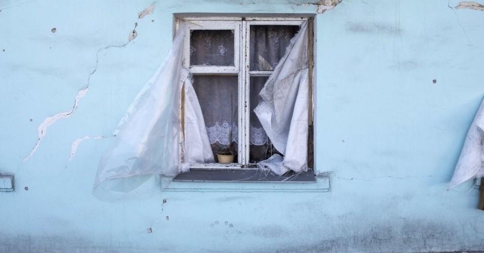 28.fev.2015 - À janela estilhaçada de uma casa na cidade de Vuhlehirsk, leste da Ucrânia, é visto um vaso de plantas abandonado. O conflito entre o Exército nacional e os rebeldes separatistas pró-Rússia deixou um rastro de destruição no local