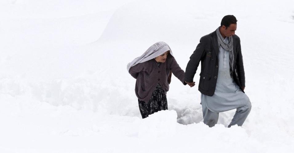 1º.mar.2015 - Afegão ajuda idosa sobrevivente de avalanche no distrito de Abdullah Khel, província de Panjshir, no Afeganistão. O número de corpos encontrados pelas equipes de chegada passa de 200