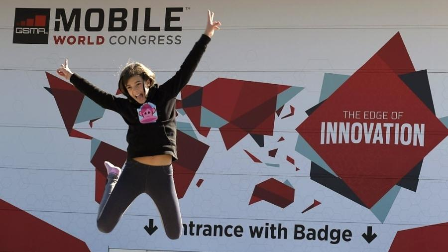 1º.mar.2015 - Garota pula em frente ao banner do Mobile World Congress 2015, realizado em Barcelona (Espanha), no primeiro dia de um dos mais importantes eventos de tecnologia de celular  - Lluis Gene/AFP