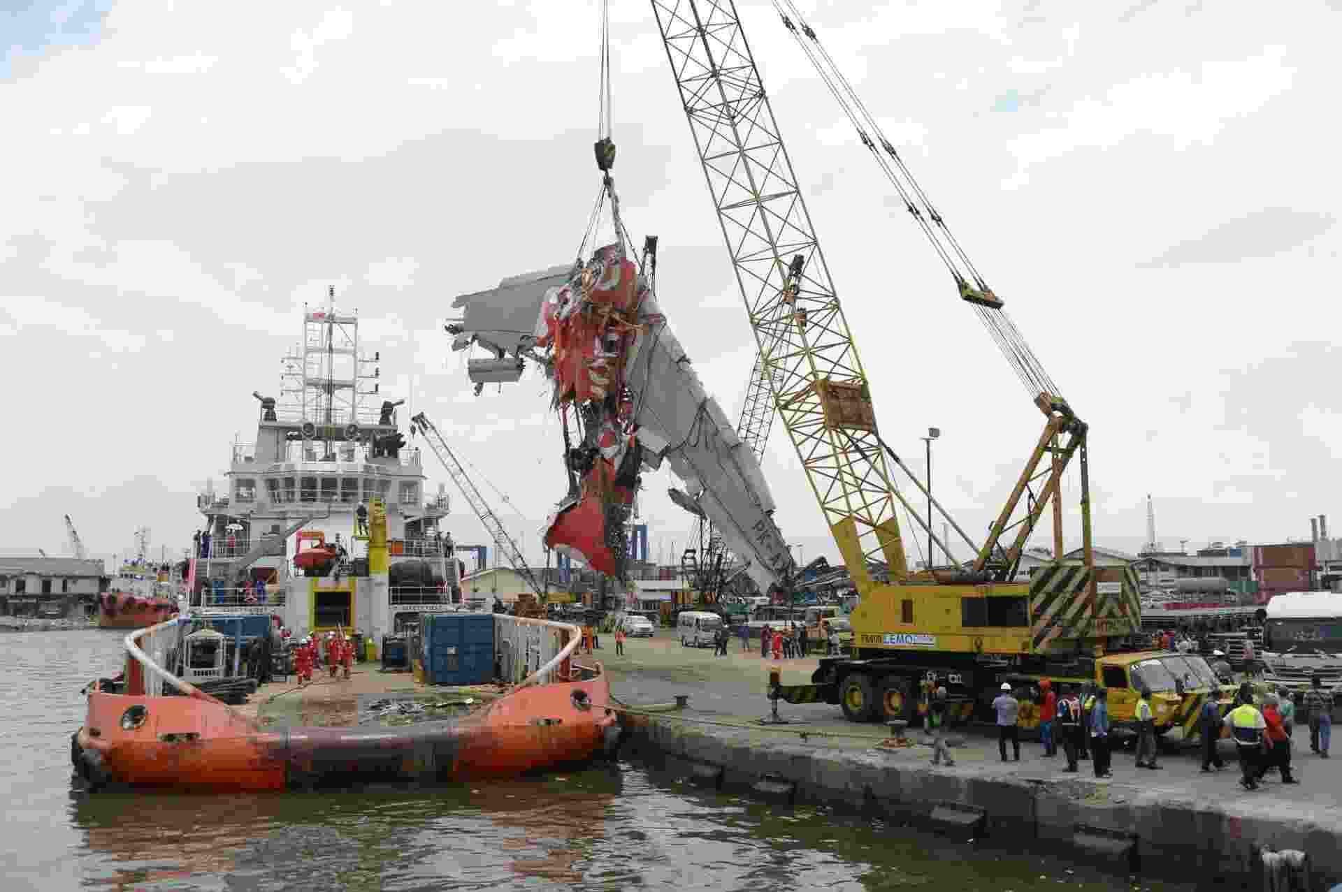 2.mar.2015 - Funcionários do governo da Indonésia removem a fuselagem do avião da AirAsia de uma embarcação no porto de Tanjung Priok, em Jacarta. O país recuperou a última grande parte do avião, do voo QZ8501, que caiu no mar de Java em dezembro, matando todas as 162 pessoas a bordo - Adek Berry/AFP