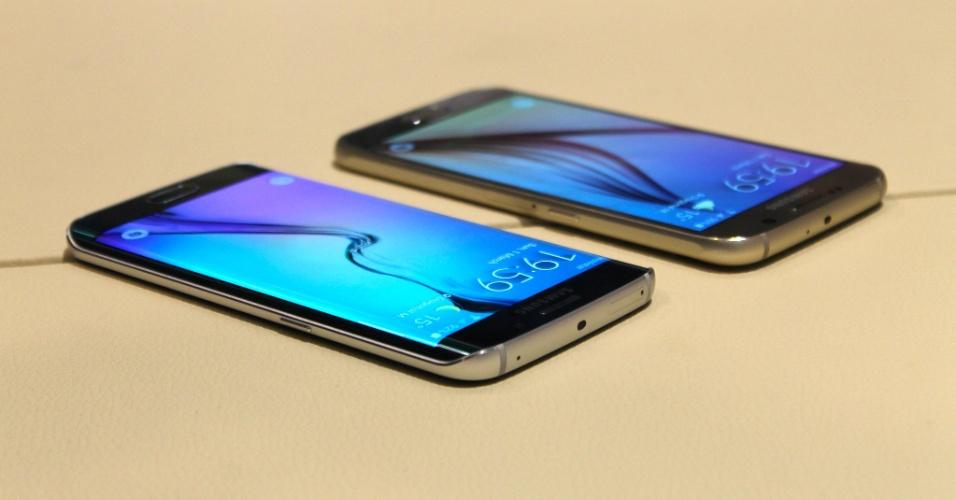2.mar.2015 - Galaxy S6 Edge (esq.) e o Galaxy S6. Os aparelhos têm praticamente a mesma configuração de hardware. A grande diferença é que o segundo conta com a tela curvada na parte frontal do dispositivo. A companhia sul-coreana acredita que desenvolveu um concorrente à altura dos iPhones 6