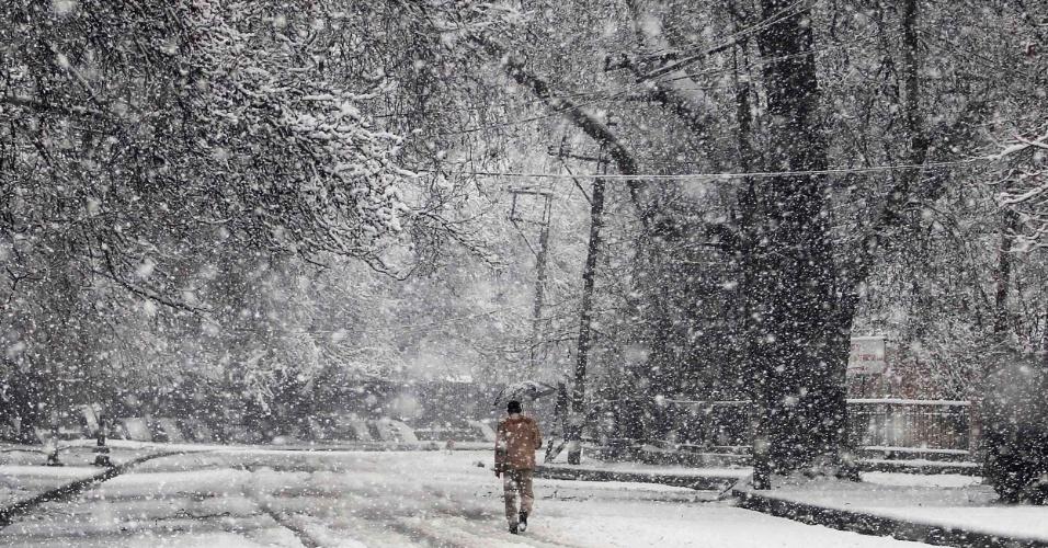 2.mar.2015 - Homem segurando um guarda-chuva anda em uma rua coberta de neve durante uma nevasca em Srinagar, na Índia