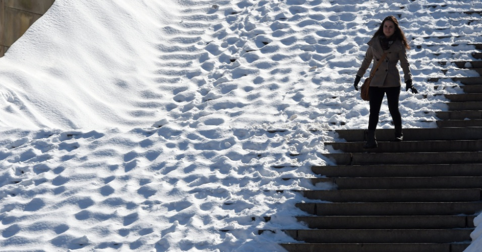 2.mar.2015 - Turista desce as escadas em Bethesda Terrace no Central Park em Nova York, onde os moradores foram surpreendidos por uma camada de mais de 15 centímetros de neve. Uma nova tempestade deve atingir a região em alguns dias, com possibilidade de acumular mais 8 centímetros de neve