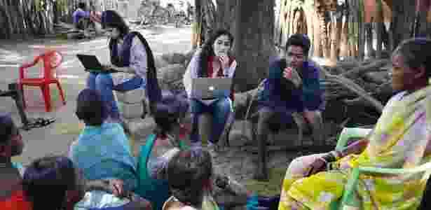 Parijata Bharadwaj e Guneet Kaur, do grupo de ajuda jurídica, com moradores do vilarejo - Kuni Takahashi/The New York Times