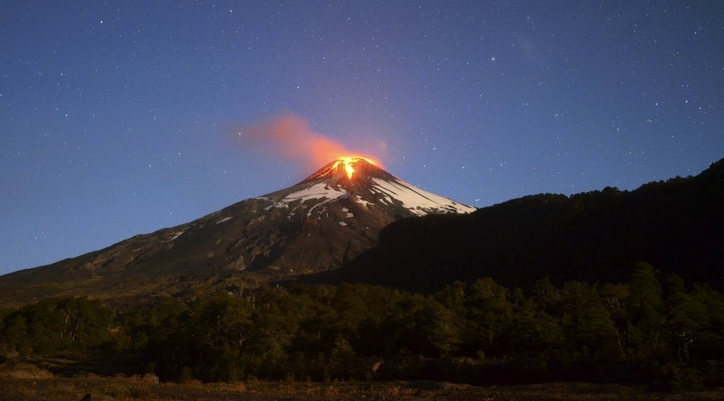 3.mar.2015 - O vulcão Villarrica, no sul do Chile, entrou em erupção na madrugada desta terça-feira (3) após 15 anos de inatividade, o que obrigou as autoridades a colocar em prática um plano de retirada preventiva da população dos arredores. O vulcão, um dos quatro mais ativos da América do Sul, fica 750 km ao sul de Santiago a uma altitude de 2.847 metros. Possui uma cratera de 200 metros de diâmetro, e entrou em erupção pela última vez em 2000