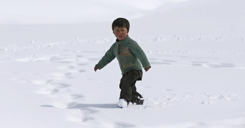 3.mar.2015 - Uma criança observa vítimas de uma avalanche recebendo insumos entregues por um helicóptero do Exército afegão, no vilarejo de Araab, distrito de Paryan, no Afeganistão, nesta terça-feira (3). O governo afegão entregou ajuda para as famílias atingidas pela avalanche na região montanhosa da província de Panjshir, onde cerca de 200 pessoas morreram na ultima semana
