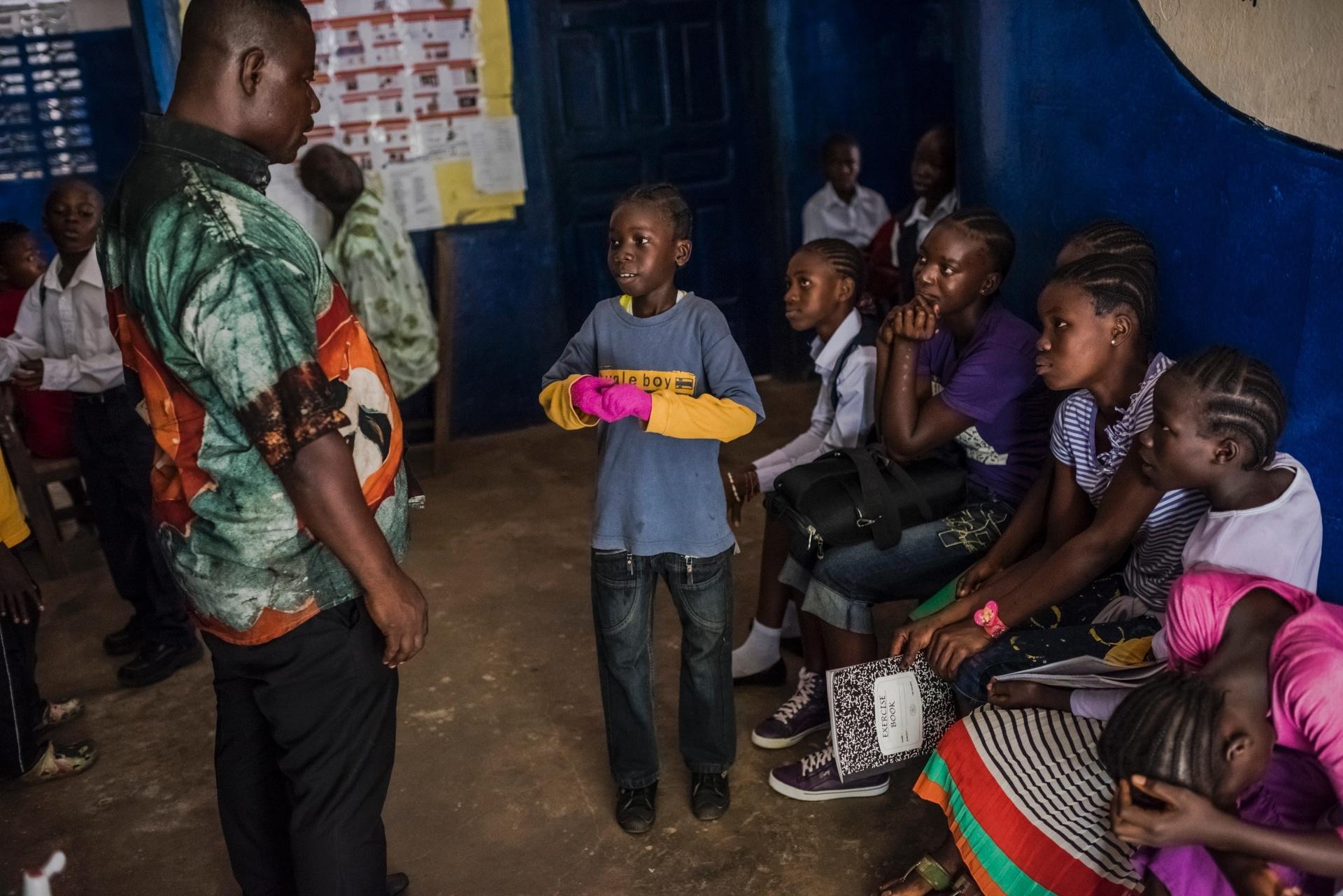 4.mar.2015 -James Nyema, 9, é questionado pelo diretor da escola, Augustus Seongbae, sobre suas luvas rosas, no primeiro dia de aula após o fechamento da escola  C.D.B. King  por oito meses devido a um surto de ebola no país