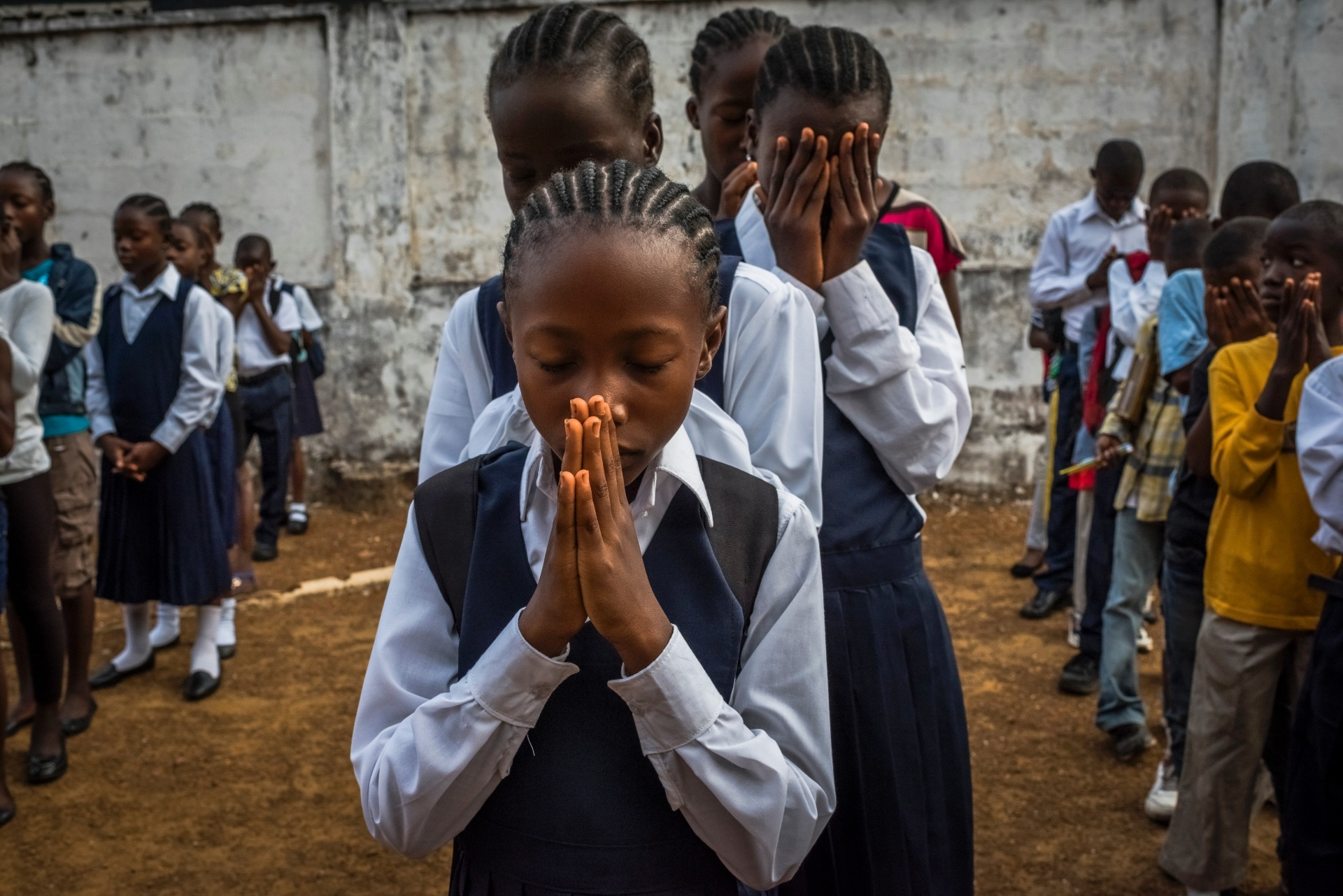4.mar.2015 -Alunos rezam durante cerimônia na reabertura da escola de ensino fundamental C.D.B King, em Monrovia, na Libéria. A escola ficou mais de oito meses fechada devido a um surto de ebola no país