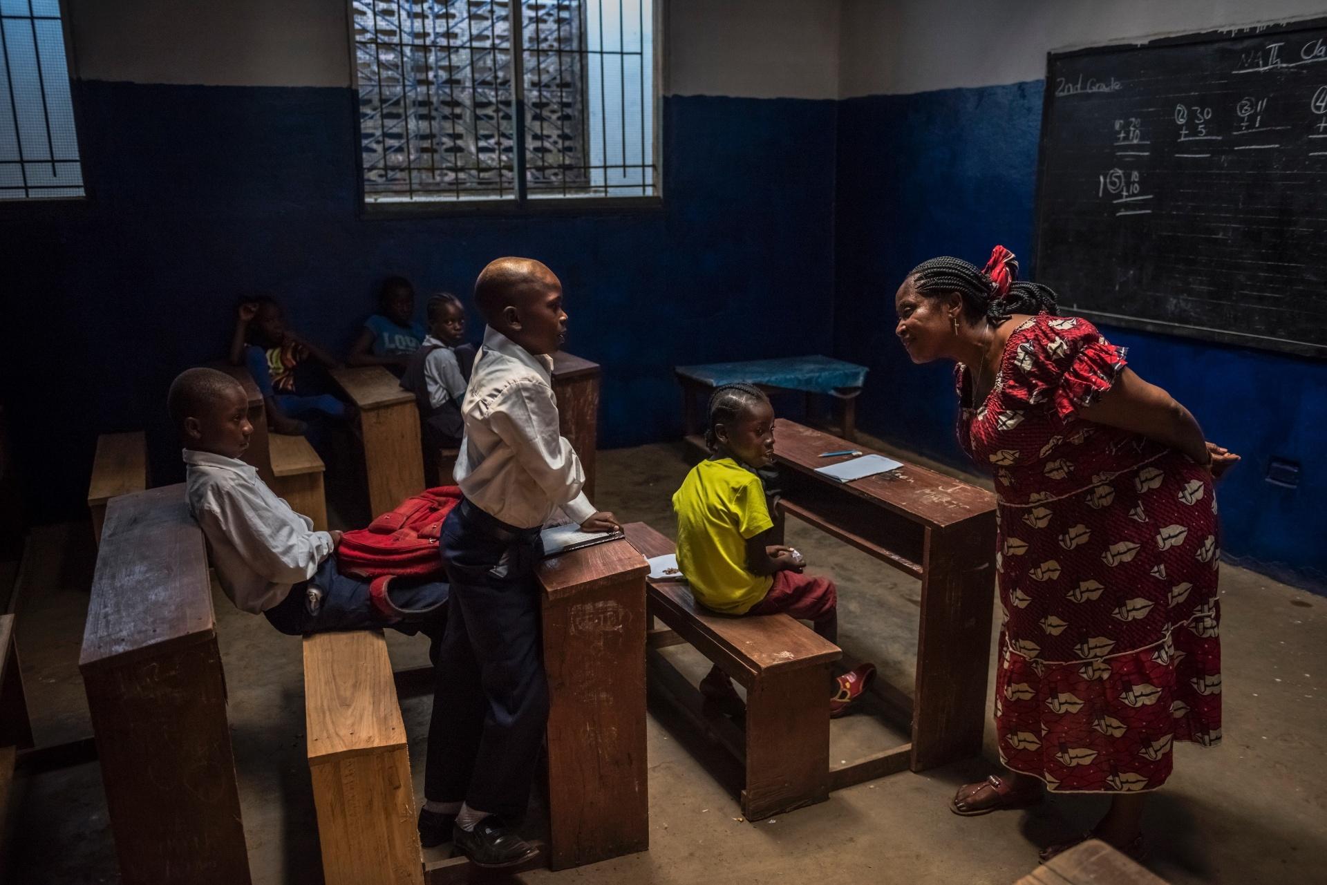 4.mar.2015 - Alunos do segundo ano do ensino fundamental ouvem a professora substituta, após um professor faltar pelo terceiro dia seguido, na escola C.D.B. King, em Monrovia, na Libéria