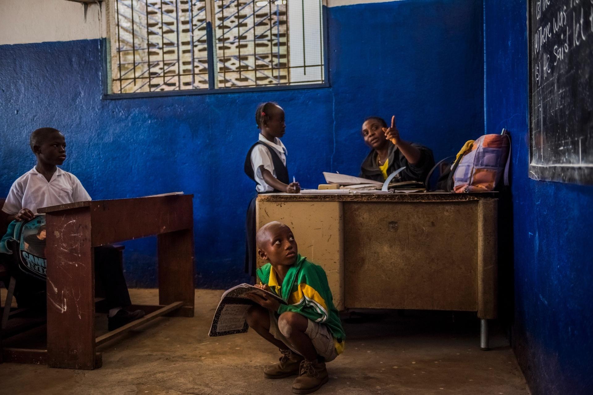 4.mar.2015 - Alunos de primeira e segunda séries estudam juntos em uma aula, devido á falta de uma das professoras, na escola de ensino fundamental C.D.B. King, em Monrovia, na Libéria