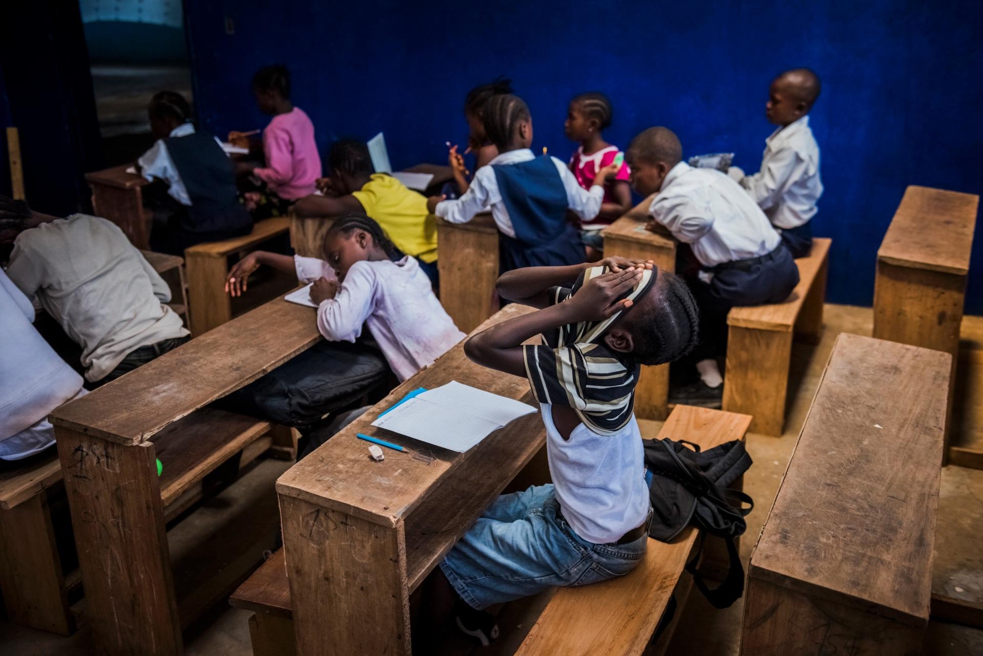 4.mar.2015 -  James Nyema, 9, cobre o rosto com a camiseta durante uma aula destinada aos alunos de primeira e segunda séries. A aula mista aconteceu devido à falta de uma das professoras na escola C.D.B. King, em Monrovia, na Libéria