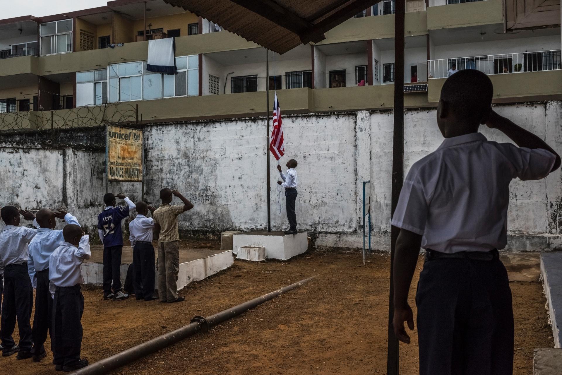 4.mar.2015 - Estudantes cantam o hino nacional da Libéria, na volta às aulas na escola de ensino fundamental C.D.B. King