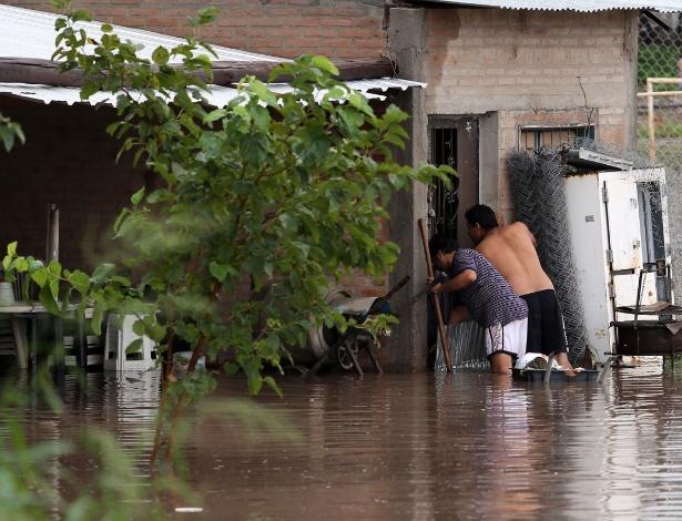 4.mar.2015 - Moradores tiram pertences de casa inundada em Santiago del Estero