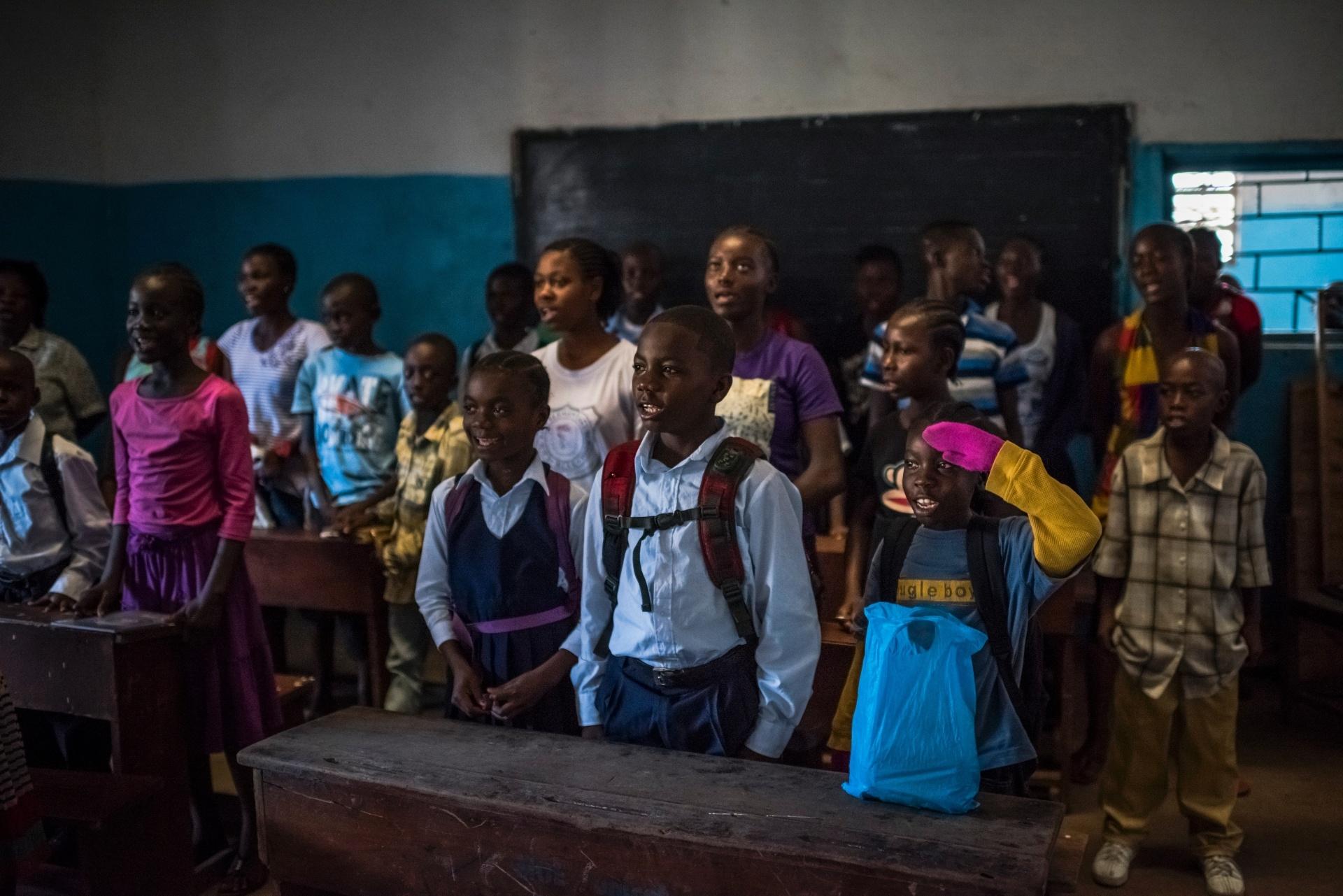 4.mar.2015 -O aluno James Nyema, 9, (de luvas rosas) canta o hino da Libéria na escola de ensino fundamental C.D.B. King, em Monrovia, na Libéria. As fotos foram tiradas em 16 de fevereiro de 2015. Apesar da epidemia de ebola ter recuado no país, diversas escolas ainda não reabriram