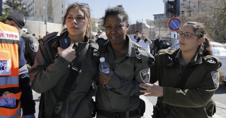 6.mar.2015 - Policial israelense é confortada por uma colega após um ataque em Jerusalém. Um motorista palestino jogou seu veículo contra um grupo de pessoas perto de uma parada de bonde em Jerusalém nesta sexta-feira (6), ferindo pelo menos cinco, incluindo quatro agentes da segurança