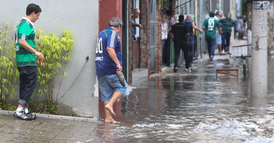 7.mar.2015 - Torcedor tira os sapatos para atravessar trecho alagado na região da Pompeia (zona oeste de São Paulo), após chuvas fortes na cidade na tarde deste sábado (7), que atrapalharam a chegada ao estádio Allianz Parque, para o jogo entre Palmeiras e Bragantino pelo Campeonato Paulista
