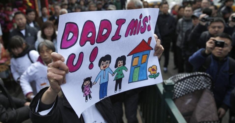 8.mar.2015 - Familiar de passageiro que estava a bordo do voo MH370, cujo desaparecimento no oceano Índico completa um ano, segura cartaz expressando a dor da perda do ente querido, em Pequim, neste domingo (8)