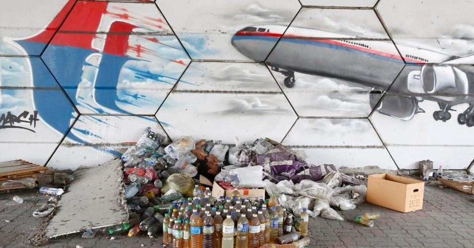 8.mar.2015 - Homem dorme embaixo de grafite que retrata o avião do voo MH370 da Malaysia Airlines em Kuala Lumpur (Malásia), quando se completa um ano de seu desaparecimento. A aeronave levava 239 pessoas a bordo. O governo malaio decidiu não realizar nenhuma cerimônia para marcar a data