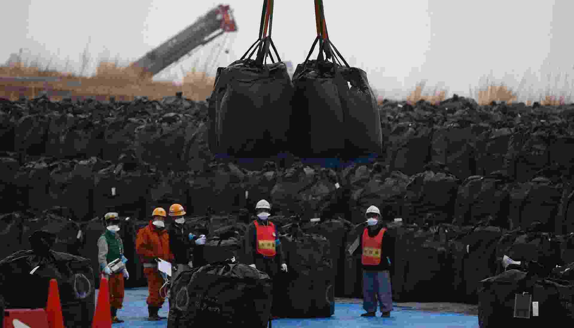 11.mar.2015 - Funcionários movimentam grandes sacos plásticos contendo terra, folhas e escombros da operação de descontaminação no centro temporário de armazenamento em Tomioka, cidade da região de Fukushima, perto da usina nuclear. Muitos moradores de Okuma, outra cidade próxima, reclamam do plano do governo do Japão de lançar cerca de 30 milhões de toneladas de escombros radioativos perto de suas casas, não acreditando na promessa do governo de Tóquio de limpar e fechar o local após 30 anos - Toru Hanai/Reuters