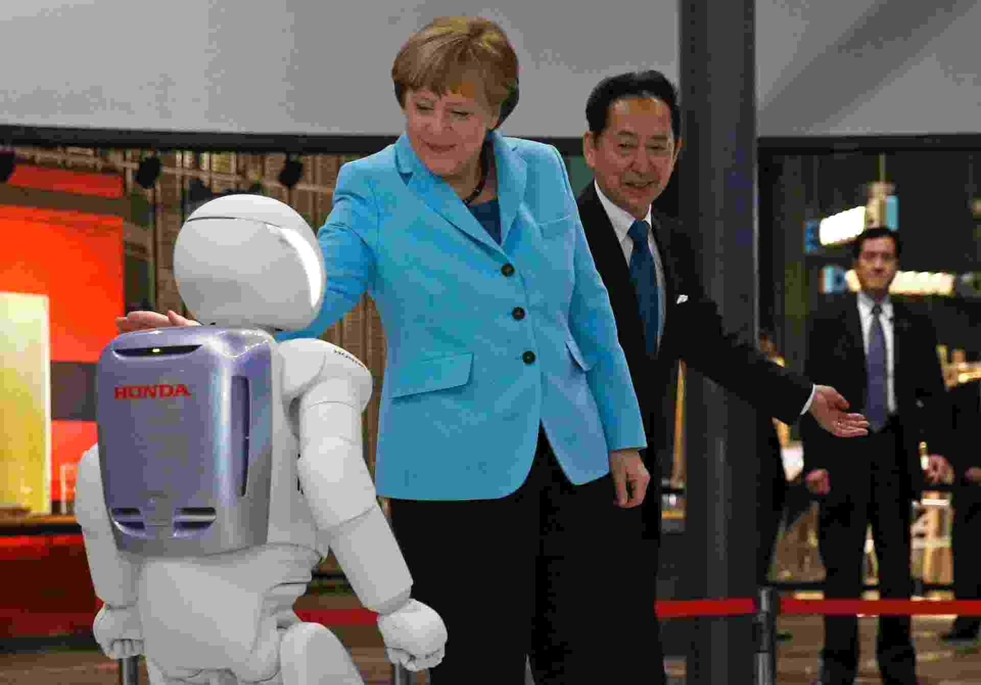"""9.mar.2015 - Ao lado Mamoru Mori, diretor-executivo do Museu Nacional de Ciência e Inovação do Japão e ex-astronauta, Angela Merkel, chanceler alemã, """"interage"""" com """"Asimo"""", um robô desenvolvido pela Honda, durante visita, em Tóquio. Merkel vai passar dois dias no país asiático - Issei Kato/Reuters"""