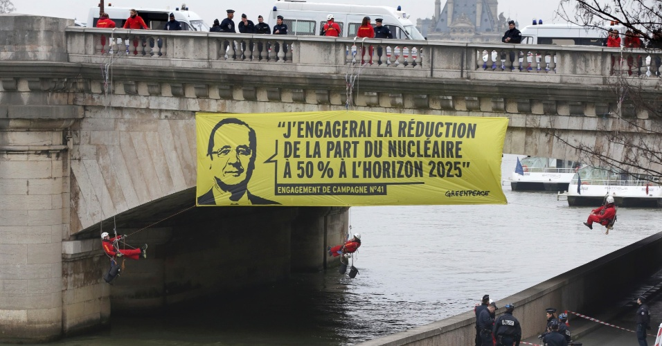 9.mar.2015 - Ativistas do Greenpeace colocaram uma faixa gigante com o retrato do presidente francês, François Hollande, com o slogan