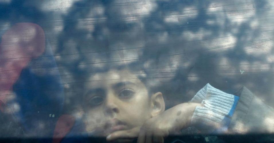 9.mar.2015 - Menino palestino observa pela janela de ônibus enquanto espera pela passagem de sua família da Faixa de Gaza para o Egito, em Rafah. Autoridades egípcias permitiram a entrada de palestinos em seu território por dois dias. Rafah é o único ponto de passagem para os moradores da Faixa de Gaza em direção ao Egito
