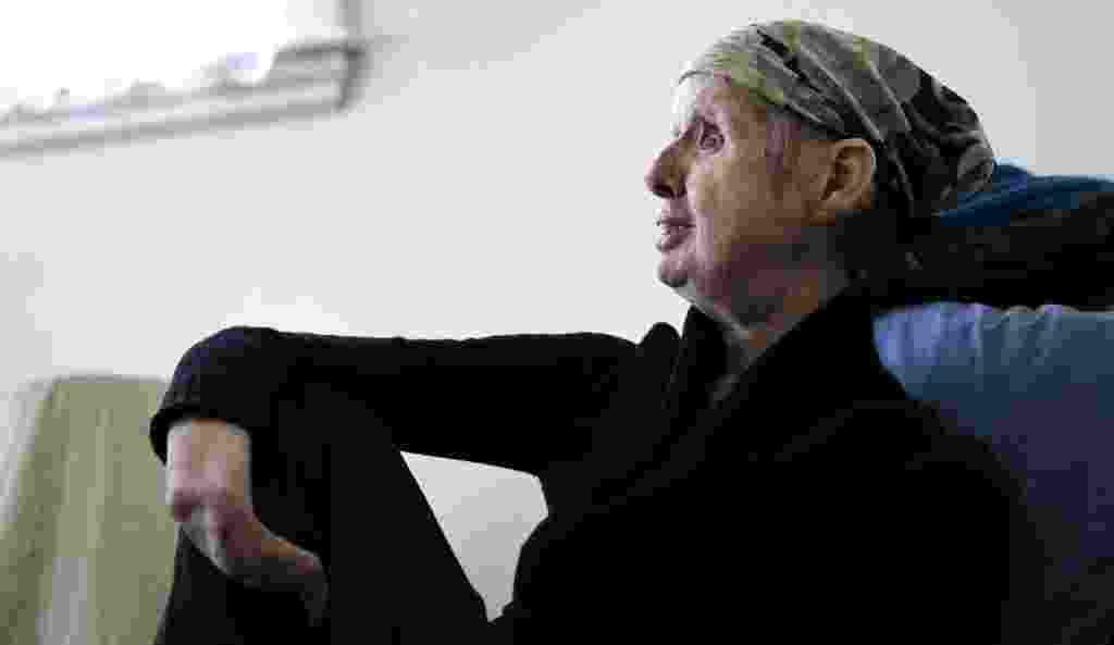 10.mar.2015 - Charla Nash senta em sua cadeira favorita no apartamento onde mora, em Boston (EUA). Nash perdeu o rosto, os olhos e as mãos depois de ser atacada por um chimpanzé em 2009. Em 2011, o Departamento de Defesa americano financiou o transplante de rosto e agora acompanha a reabilitação dela. Os estudos podem ajudar soldados gravemente desfigurados que retornam da guerra - Charles Krupa/AP