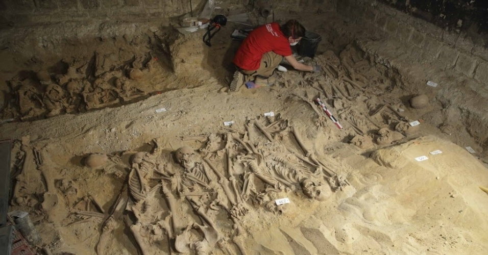 11.mar.2015 - Arqueólogo trabalha no local onde foram encontrados oito valas coletivas com mais de 200 esqueletos sob um supermercado em Paris