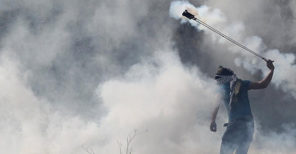 11.mar.2015 -  Manifestante palestino atira de volta uma bomba de gás lacrimogêneo lançada por policiais israelenses durante confrontos na sequência de uma manifestação de estudantes da Universidade de Birzeit, perto de Ramala. O protesto é contra a prisão de estudantes universitários palestinos