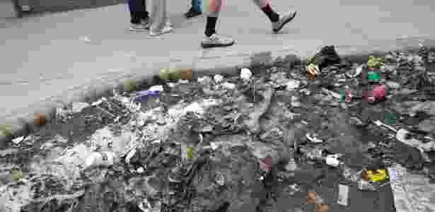 Pedestres passam por lama e lixo revelados com o derretimento da neve no começo de março, em Nova York - James Estrin/The New York Times