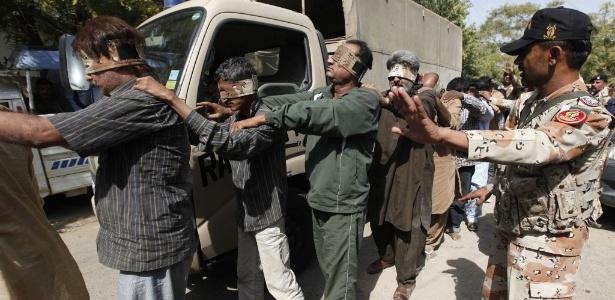 12.mar.2015 - Soldado guia homens vendados até um tribunal antiterrorismo em Karachi