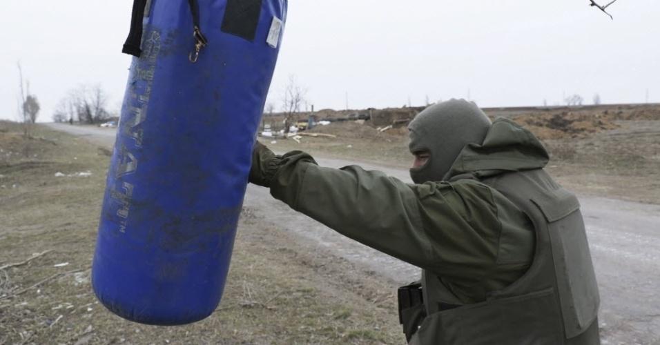 12.mar.2015 - Soldado ucraniano treina com um saco de boxe na cidade de Shyrokino, perto de Mariupol, no leste do país. Os separatistas pró-Rússia denunciaram a concentração de tropas do governo na periferia da cidade de Mariupol, na região de Donetsk, e acusaram o governo de violar o cessar-fogo
