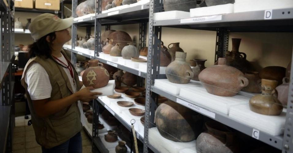 12.mar.2015 - Um arqueólogo organiza cerâmica pré-incaicas em prateleiras do museu Puruchuco, em Lima, no Peru
