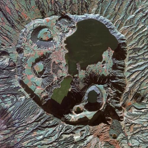 13.mar.2015 - A ilha de São Miguel, do arquipélago dos Açores, em Portugal dispõe de um complexo vulcânico chamado de Lagoa das Sete Cidades. A cratera que domina a imagem mede cerca de 5 km de diâmetro. No interior, há lagos, cones vulcânicos, domos de lava e crateras alagadas. A Lagoa das Sete Cidades é composta por dois lagos que são conectados por uma passagem estreita, visível no centro da imagem. O lago ao norte é conhecido como o lago Azul, enquanto o outro, no sul, é o lago Verde, de acordo com a coloração de cada um. Na área circundante, podemos ver as linhas distintas onde a vegetação cresce ao longo das vias. Entre essas linhas há terrenos agrícolas. A imagem foi feita em 6 de dezembro de 2014