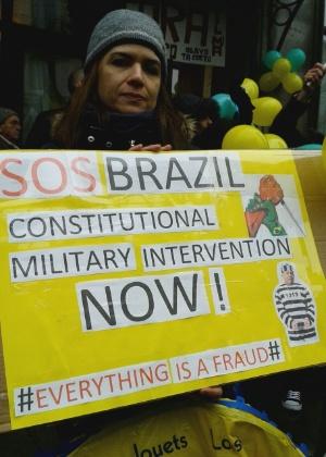 15.mar.2015 - Manifestante mostra cartaz em protesto contra o governo brasileiro em Londres, capital da Inglaterra. Na faixa, pede-se intervenção militar no Brasil e a prisão do ex-presidente Lula