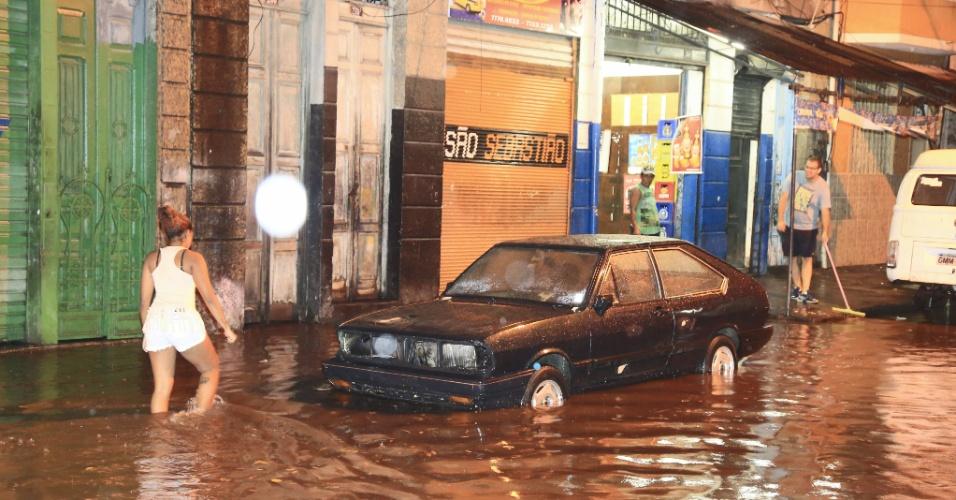 16.mar.2015 - Moradora enfrenta alagamento na rua Senhor dos Matosinhos, na Cidade Nova, centro do Rio de Janeiro, a noite desta segunda-feira (16), após forte chuva atingir a capital fluminense