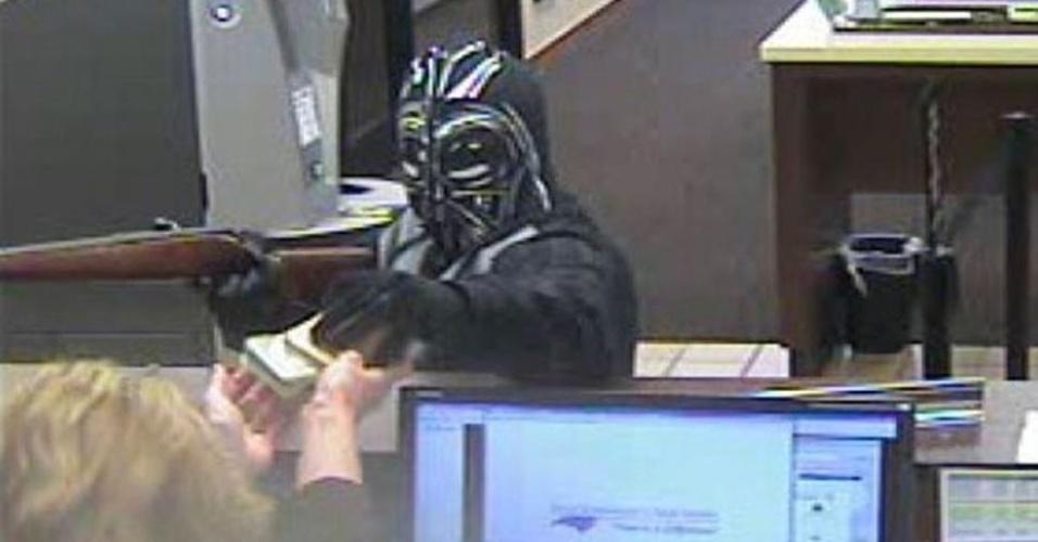 17.mar.2015 - Um homem vestindo uma máscara de Darth Vader e roupas pretas roubou um banco de Pineville, na Carolina do Norte. A polícia e o FBI estão tentando identificar o suspeito, que está foragido. O mascarado entrou no banco com uma arma de cano longo e pediu dinheiro para uma bancária, ele fugiu em uma SUV. Não foi divulgado quanto dinheiro foi roubado