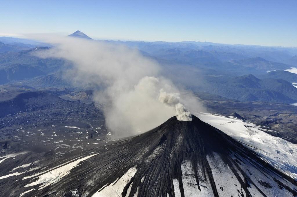 18.mar.2015 - Vista aérea mostra fumaça e cinza expelidas do vulcão Villarrica, no sul de Santiago (Chile), nesta quarta-feira (18). A atividade sísmica do vulcão aumentou nas últimas horas o que fez com que as autoridades elevassem de amarelo para laranja o nível de alerta preventivo