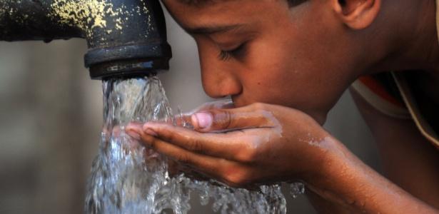 Uma criança bebe água de uma bomba manual em um bairro pobre de Karachi, no Paquistão - Rizwan Tabassum/AFP
