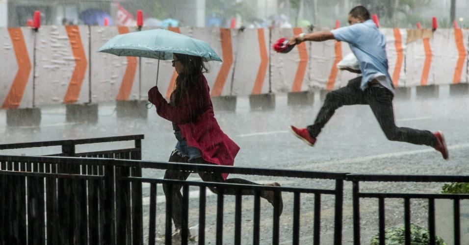 20.mar.2015 - Chuva forte causa pontos de alagamento na avenida Paulista, na área central de São Paulo, fazendo com que pedestres tivessem de pular para atravessar a rua ou se esconder sob as marquises