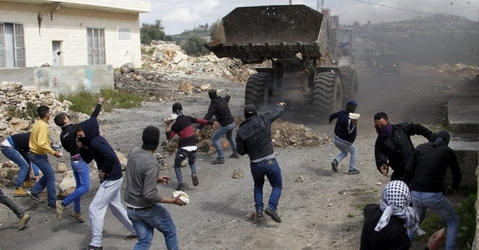 20.mar.2015 - Palestinos atiram pedras contra uma escavadeira durante um confronto com tropas israelenses na cidade de Kofr Qadom , perto de Nablus, na Cisjordânia. O confronto aconteceu depois de uma manifestação contra os assentamentos israelenses em Qadomem. Segundo a imprensa local, cinco palestinos foram feridos