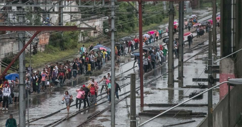 20.mar.2015 - Usuários da CPTM (Companhia Paulista de Trens Metropolitanos)são obrigados a andar pelos trilhos na estação Brás, no centro de São Paulo. A circulação dos trens foi paralisada devido a alagamentos provocados pela forte chuva que cai sobre a capital paulista nesta sexta-feira (20)