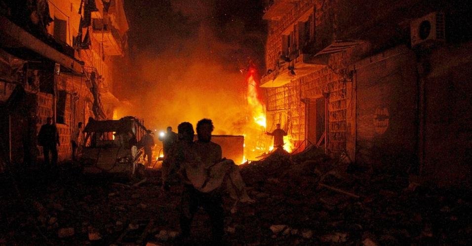 20.mar.2015 - Sírio carrega colega ferido depois de bombardeio sobre o bairro de Al-Mashhad, em Aleppo, na noite desta sexta-feira (20). Ativistas acusam as forças leais ao ditador da Síria, Bashar Assad, de lançar bombas cluster sobre os edifícios