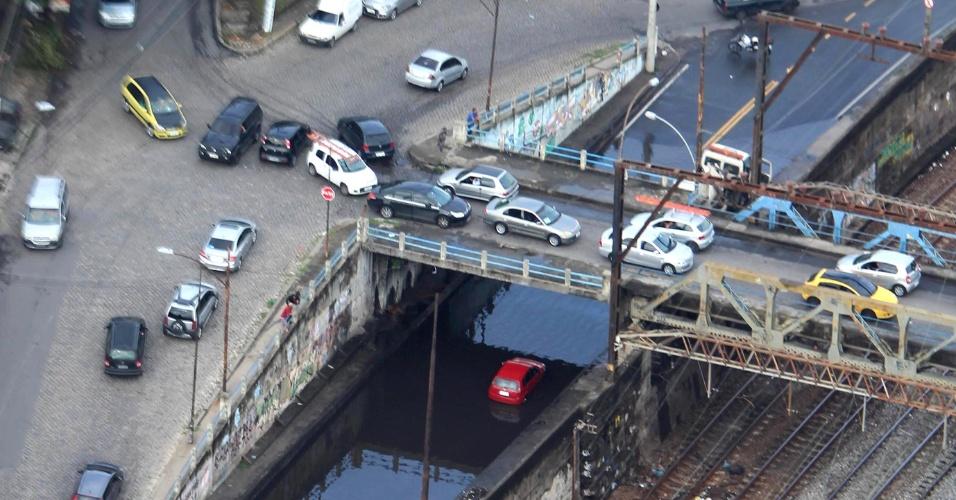 23.mar.2015 - Carro fica submerso na rua Elias da Silva, em Quintino, na zona norte do Rio de Janeiro, na manhã desta segunda-feira, em razão das fortes chuvas que atingiram a região no domingo