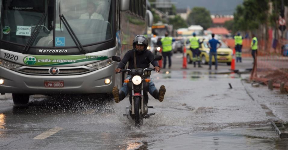 23.mar.2015 - Motociclista e ônibus passam pela avenida Professor Pereira Reis, no bairro de Santo Cristo, na zona portuária do Rio de Janeiro, que continua alagada após chuvas que atingiram a cidade no domingo (22)