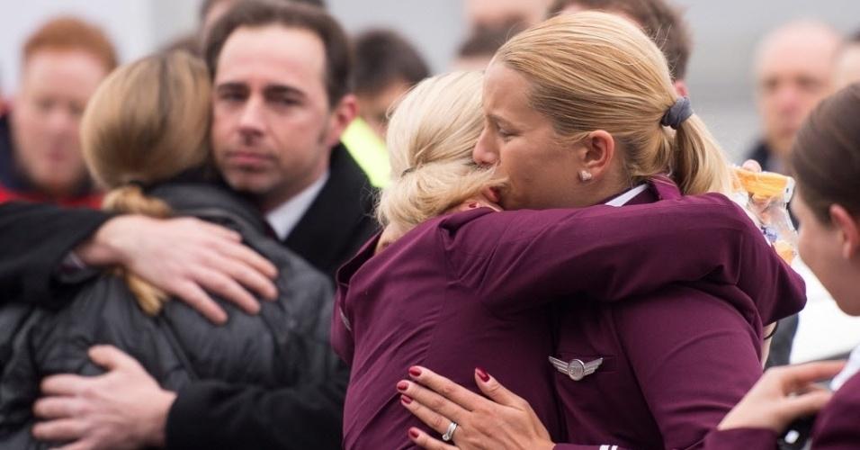 25.mar.2015 - Funcionários da companhia aérea alemã Germanwings se abraçam em frente à sede da empresa em Colônia, na Alemanha, em homenagem às vítimas do voo que caiu nos Alpes franceses. A Germanwings, que operava o Airbus A320 acidentado com 150 pessoas a bordo, é uma subsidiária da Lufthansa