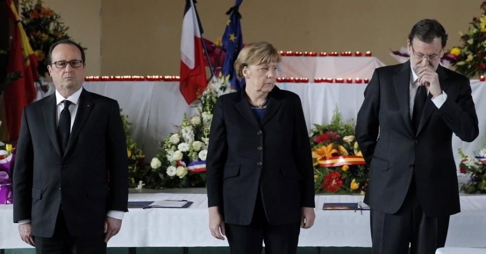 25.mar.2015 - O presidente francês, François Hollande (à esq.), a chanceler alemã, Angela Merkel (no centro), e o primeiro-ministro espanhol, Mariano Rajoy (à dir.), prestam homenagem em necrotério improvisado preparado para as 150 vítimas que morreram em um acidente de avião nos Alpes franceses