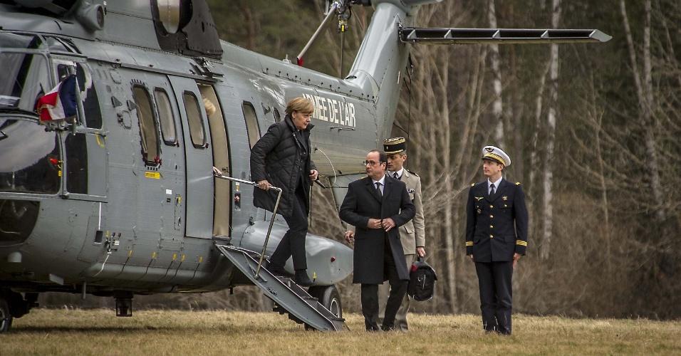 25.mar.2015 - O presidente francês, François Hollande aguarda a chanceler alemã Angela Merkel desembarcar do helicóptero que os levou até a região onde caiu o Airbus A320 da Germanwing