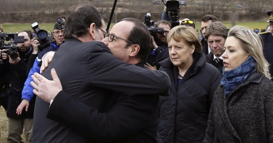 25.mar.2015 - O primeiro-ministro da Espanha, Mariano Rajoy (esq.), abraça o presidente da França, François Hollande, na presença da chanceler alemã, Angela Merkel. Os chefes de Estado visitam o local da queda do avião da Germanwings nos Alpes franceses