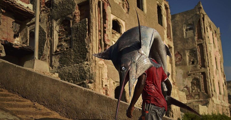 25.mar.2015 - Um homem carrega um peixe espada pelo distrito Hamarweyne, no sul de Mogadíscio, na Somália